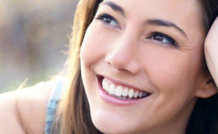 An Ahwatukee woman smiles widely to show off her new dental veneers.