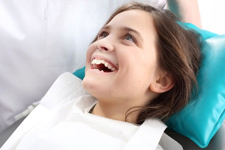A pediatric dental patient smiles while waiting for treatment.