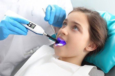 A dentist applies a sealant to a young girl in Ahwatukee, Arizona.
